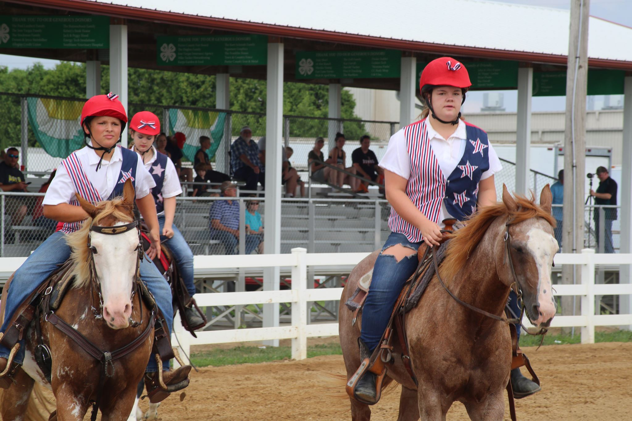 Three horses and riders at a horse show