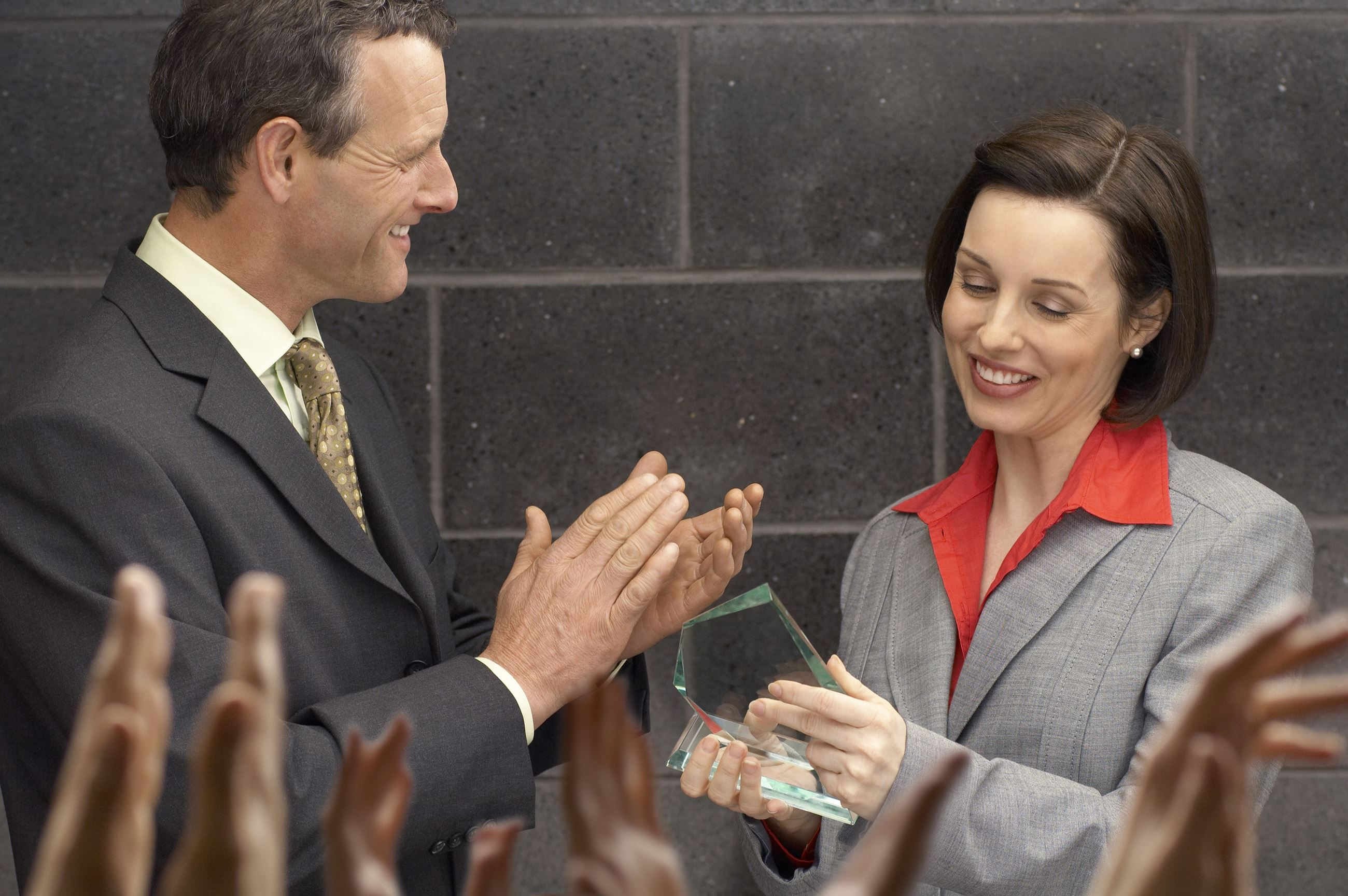 Man applauding a woman that has received an award