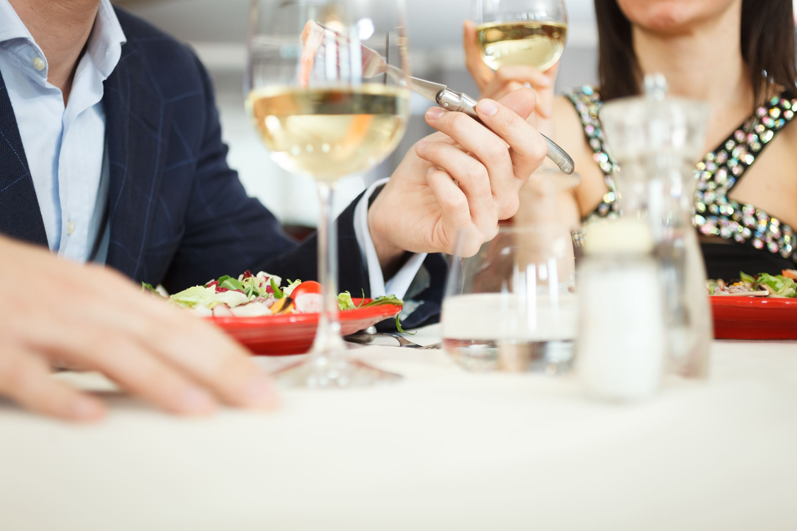 Man and woman at a table eating and sipping wine